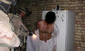 A prisoner in Iraq, held at gunpoint by US soldiers. Credit: AP