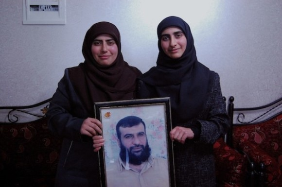 Sisters Doha Ibrahim Abeyat (left) and Hind Ibrahim Abeyet hold a framed photo of their father, Ibrahim Abeyet, who was deported from the West Bank to Italy in 2002. Credit: Jillian Kestler-D'Amours/IPS.
