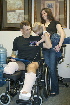 Todd E. Hammond shows his Purple Heart medal to his two-year-old daughter (credit: U.S Navy)