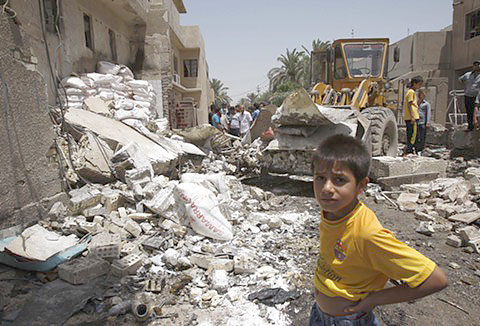 A boy surveys the aftermath of a bombing in Baghdad in June