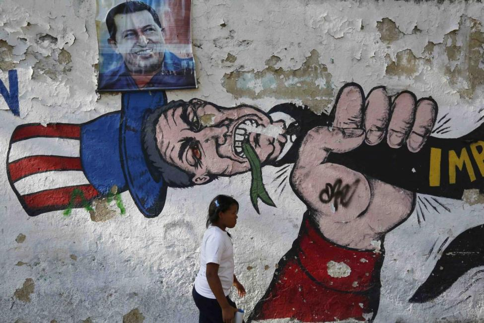 A Venzuelan woman walks by anti-American graffiti and a portrait of Hugo Chavez in Caracas.