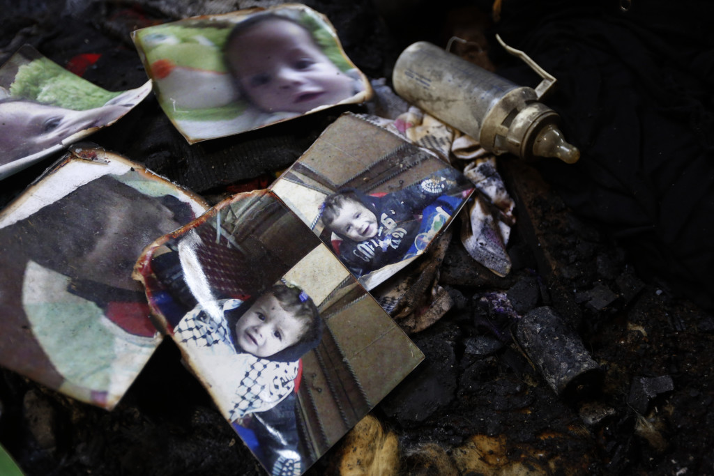 Burnt photographs of 18-month-old Ali Dawabsha are seen in Ali's fire damaged room in the West Bank village of Douma near Nablus City, 31 July 2015. The Palestinian infant was killed and several people injured when their home was set alight in the northern West Bank early 31 July 2015, an official said. A group of masked people believed to be Israeli settlers threw flammable bombs into two houses on the outskirts of the village of Doma, south of Nablus, said Ghassan Daghlas, a Palestinian Authority official.  EPA/ALAA BADARNEH